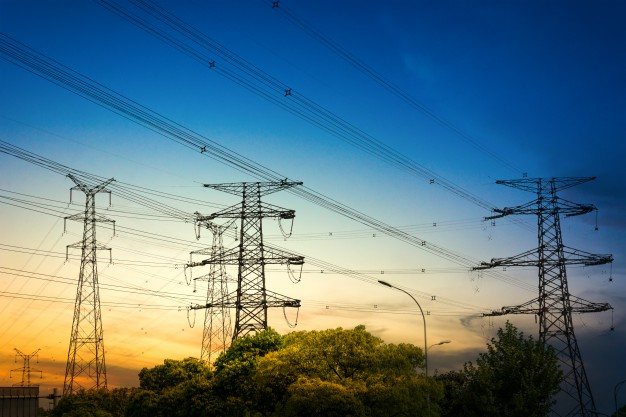 sun-setting-behind-the-silhouette-of-electricity-pylons_1127-2986